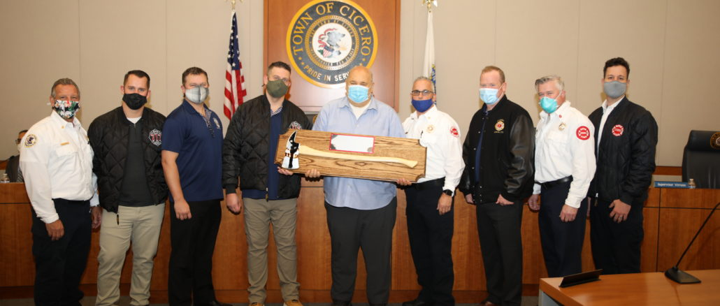 "Town President Larry Dominick receives a ""Fiefighter's Axe"" from the Cicero Firefighters and from union leaders for his strong support of the Fire Department. Photo courtesy of the Town of Cicero and Gerardo Lopez."